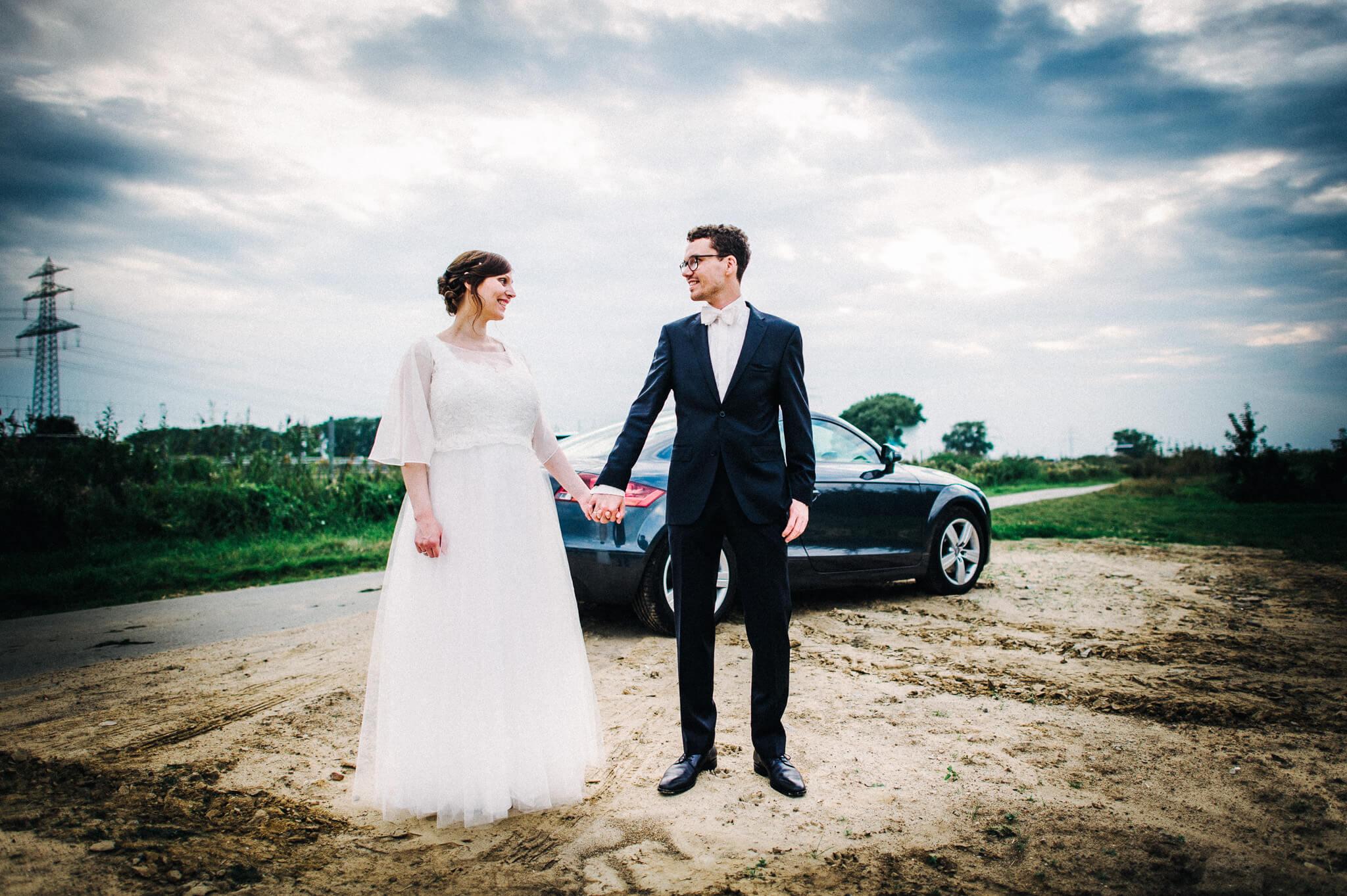 Brautpaar mit Audi TT auf einem Feld